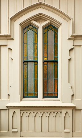 Simple Stained amber Church window bordered in green on a gothic wood wall Banco de Imagens