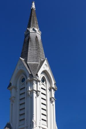Sunny Steeple on a christian church against blue sky Banco de Imagens