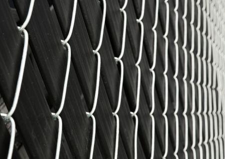 Black plastic strips imbedded into cyclone fence taken with extreme diminishing shot Stock Photo - 17593126