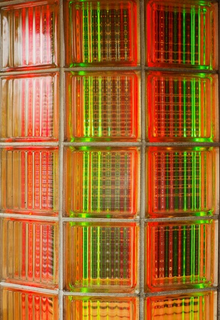 Curved glass brick wall lit from behind with red and green neon lights