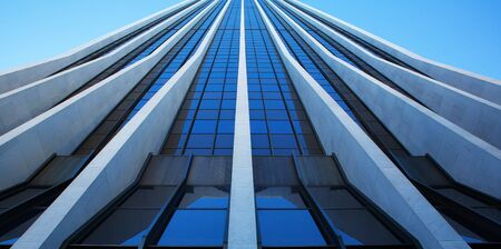 Close up vertical view of modern office building on a clear day that looks like a speed ramp to the sky Banco de Imagens