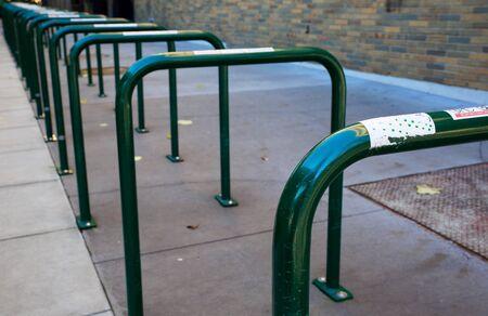 Row of empty green painted bike Racks at university Banco de Imagens