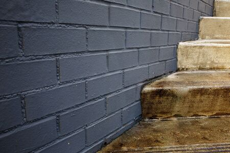 Abstract of concrete outdoor stair case intersecting gray block wall Banco de Imagens
