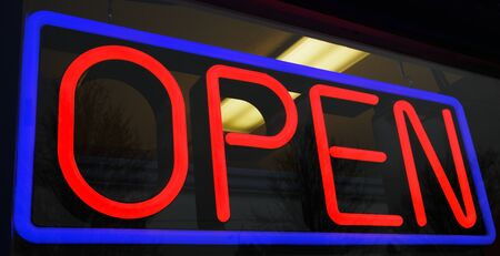 Red and blue neon open sign at store with background interior lights photo