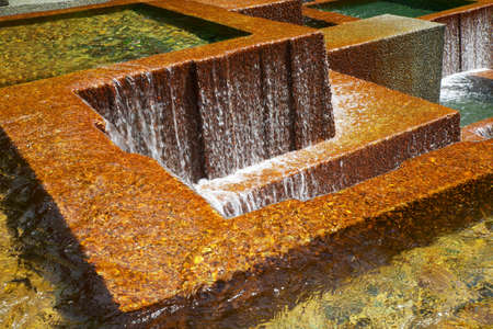 Multiple pools with water falls over golden concrete walls