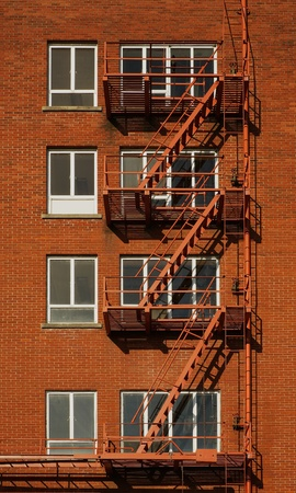 Red brick building with four rows of windowed fire escapes
