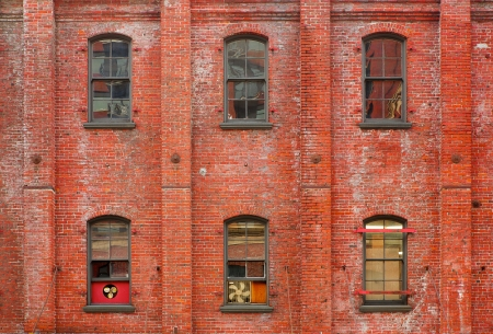 Three columns of windows on an old brick walled building