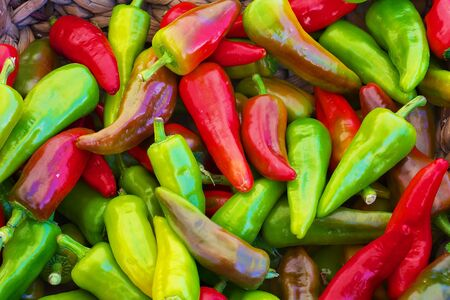 red green yellow purple hot Peppers at the farmers market with sharp focus on center vegetables Banco de Imagens