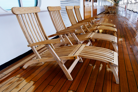 Diminishing view of a row of deck chairs on a cruise ship with a wet teak wood floor