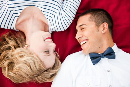 a close-up of a couple laying on a red picnic blanket Stock Photo - 8138756