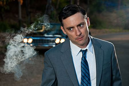 A young stylish business man clouded by smoke and walking away from a vintage car in a shadowy outdoor scene Stock Photo - 8138017