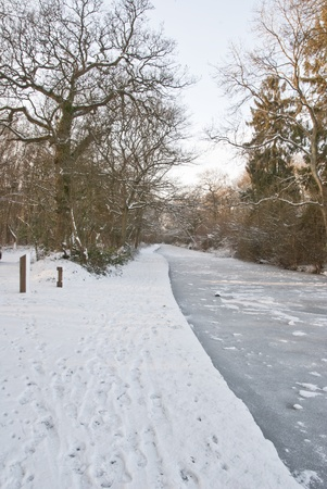 Frozen canal in mid-winter with trees in background and snow covered towpath Stock Photo