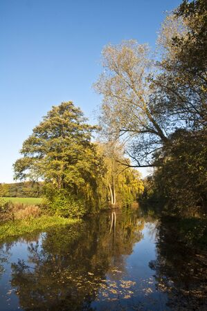 Small lake with trees in autumn colours and clear blue sky Stock Photo