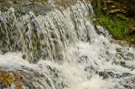Water forming small waterfalls in a mountain stream