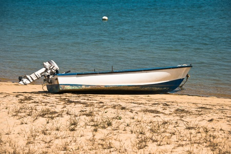 Small Boat with Outboard Motor on a Beach