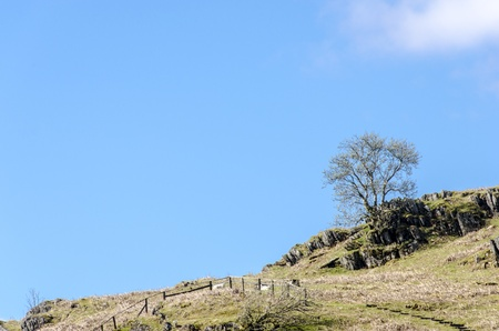 Rocky scrub land at the top of a hill against blue sky