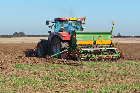 Farmer in tractor with seed planter sowing a new crop