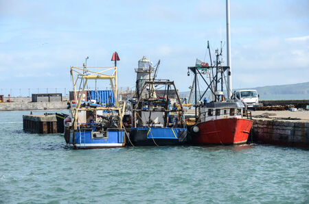 Three fishing boats tied up in harbour Stock Photo