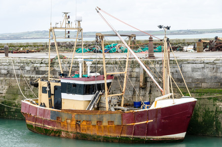 Rusty old fishing boat tied up in harbour