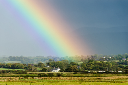 Rainbow appearing to end over a house Stock Photo