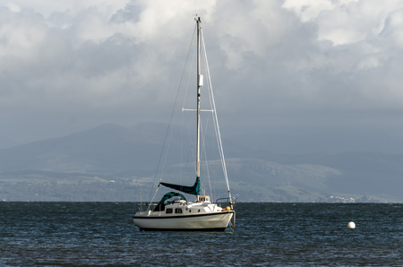 furled: Yacht at anchor in a bay Stock Photo