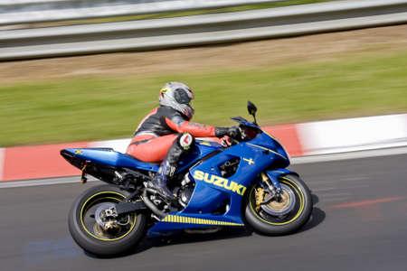 kerb: Motor biker on a race circuit speeding round a corner with a race circuit kerb behind