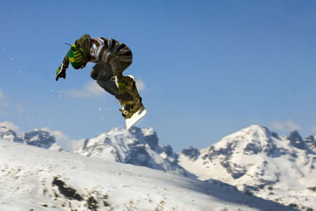 Snowboarder  jumping over the snow-mountain.
