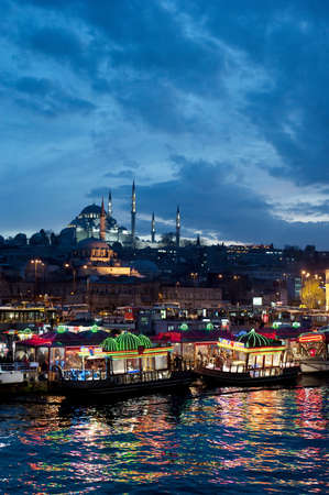 bosporus: Istanbul skyline from Galata bridge by night, with Suleymaniye mosque and fish boat restaurants in Eminonu