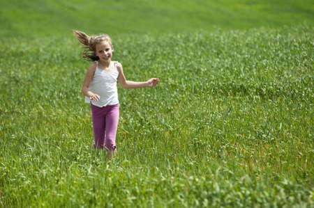Little happy girl running on green meadow field  photo