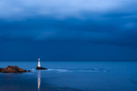 nightly: Nightly seascape with lighthouse and moody sky