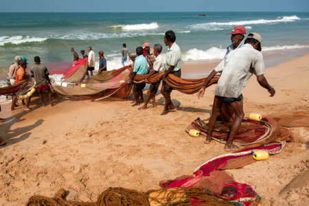india fisherman: GALLE, SRI LANKA - DECEMBER 31 , 2014: Group of local fishermans pulling net from the ocean. Editorial