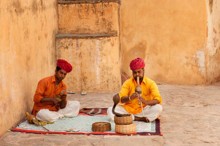 rajhastan: JAIPUR INDIA  APRIL  22 2015: A snake charmer is playing the flute for the cobra sitting by the wall in the Fort Amber on April 22 2015 in Jaipur India. Editorial