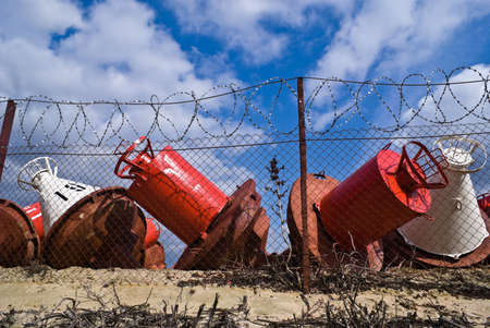 River buoy over a wire fence on a background of blue sky photo