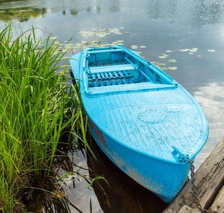 rowing boat: Blue metal rowing boat on the background of the river and the green plants