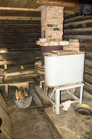 finnish bath: Rustic bathhouse inside with wood stove and basin