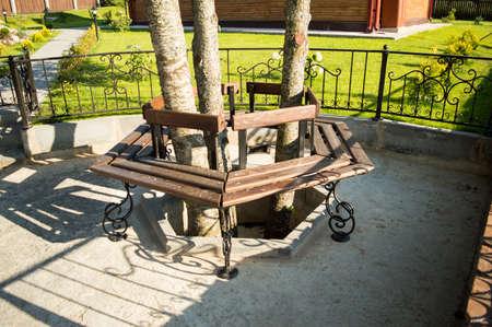 legs around: Wooden bench with iron legs around the three trees. Sunny day. Stock Photo