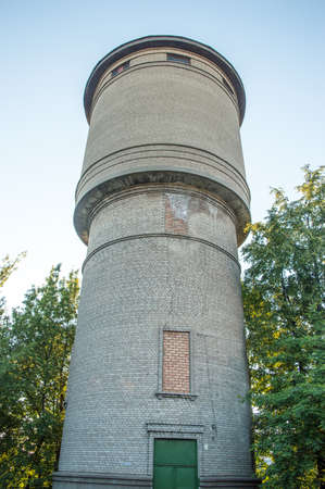 old style white bricks water tower on background trees Imagens