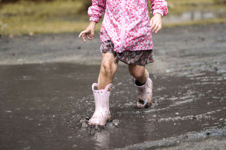 Sute little girl in pink raincoat and rubber boots is jumping in a muddy puddle. Autumn mood photo