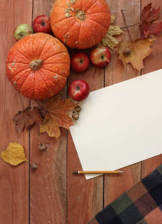 a place of life: Autumn still life with pumpkins, leaves and apple on old wooden background, paper place for text Stock Photo