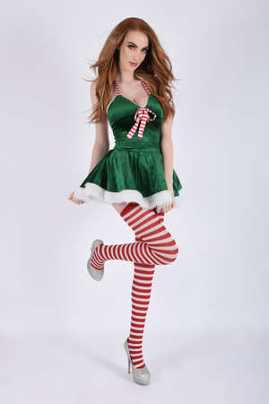 Attractive, slender, redhead model dressed as a elf for Christmas, isolated against a white background