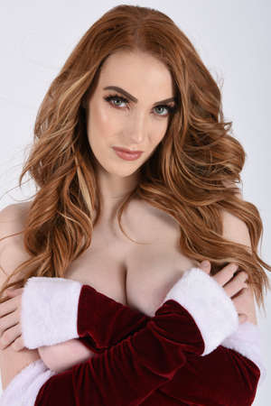 Beautiful, tall, slim, busty, redhead model dressed in a variety of Christmas outfits, isolated against a plain background
