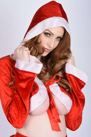 Beautiful, tall, slim, busty, redhead model dressed in a variety of sexy Christmas outfits, isolated against a plain background