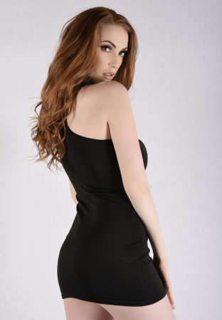 Beautiful, tall, slim redhead model wearing a short black dress, isolated against a grey background 写真素材