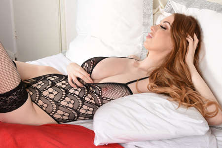 Attractive, tall, busty, redhead model dressed in a black lace bodysuit, lying on her bed Foto de archivo