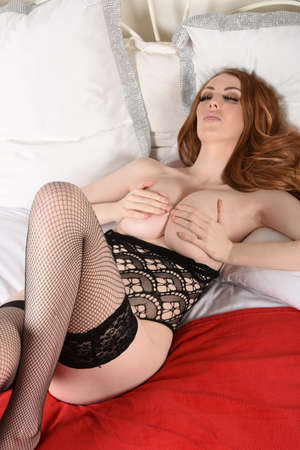Attractive, tall, busty, redhead model dressed in a black lace bodysuit, lying on her bed