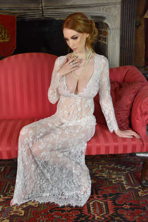 Beautiful, tall, redhead model dressed in a lace dress and pretty pink lingerie, in an old house Imagens