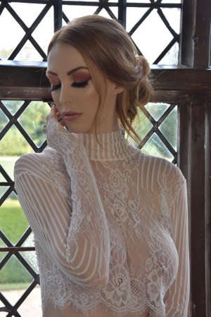 Beautiful, tall, redhead model dressed in a lace dress and pretty pink lingerie, in an old house Foto de archivo