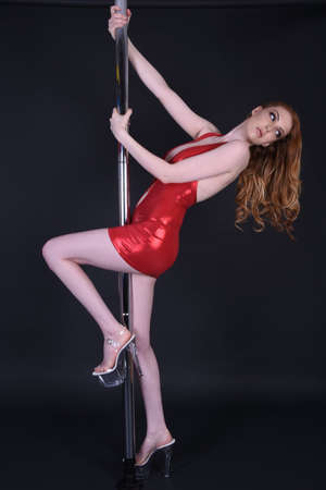 Beautiful, tall, sexy, redhead model dressed as a Poledancer in a tight, red dress, isolated against a black background Standard-Bild