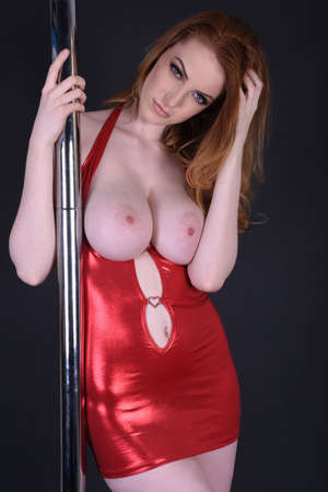 Beautiful, tall, sexy, redhead model dressed as a Poledancer in a tight, red dress, isolated against a black background