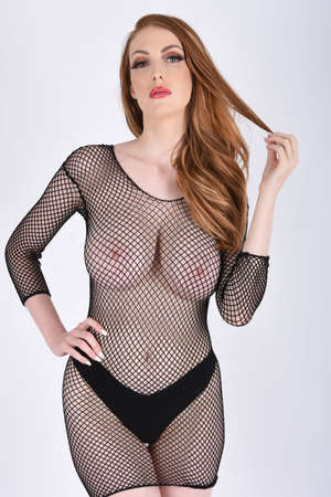 Beautiful, tall, redhead model dressed in a black mesh bodysuit,isolated against a white background Imagens